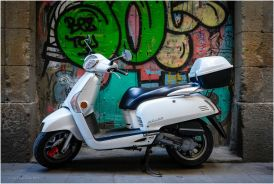 I found this bike parked in a dark alley, I liked the white against the colourful graffiti.